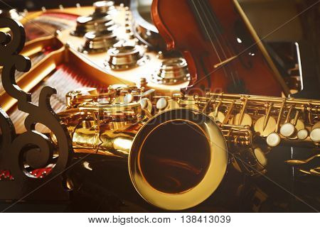 Violin and saxophone lying on piano, close up