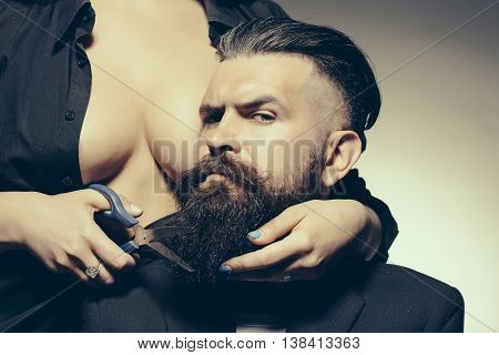 Young handsome man with long beard and moustache on serious face with female beautiful bare chest of young woman cutting with scissors