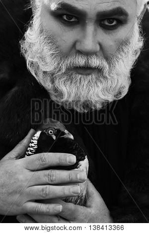 old bearded man with long white beard on serious face with makeup in fur coat holding colorful pheasant bird sunny day outdoor black and white