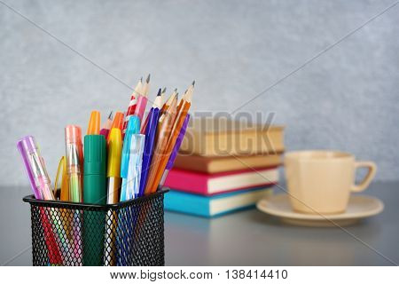 Colorful pencils and pens in metal holder on grey wall background