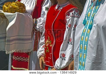 People in traditional Ukrainian costumes awaiting guests with bread.