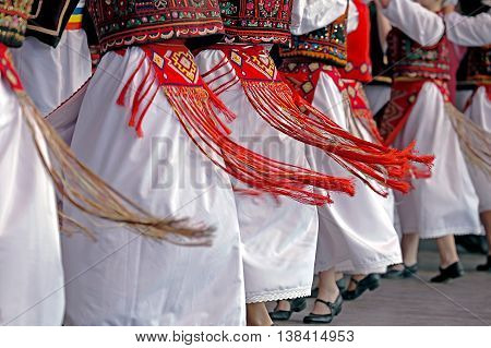 Romanian dancers in traditional costume perform a folk dance.