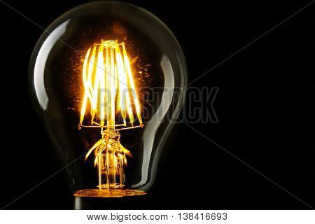 Illuminated light bulb on black background