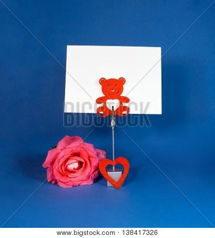 Note holder with rose and empty card on blue