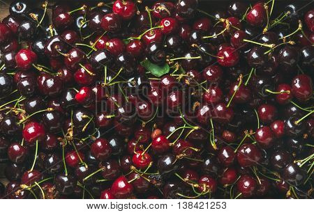 Background of dark red sweet cherries over wooden backdrop. Top view, horizontal composition