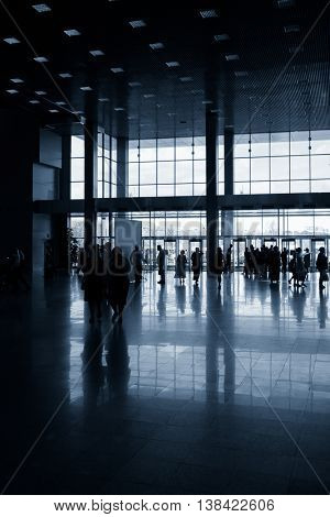 Silhouettes of people in modern lobby