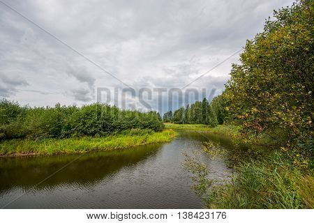 Clouds over river in mid day. Nature landscape.