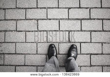 Male Feet Standing On Gray Cobblestone Road
