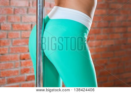 Young fitness woman standing back to a pole in the gym.
