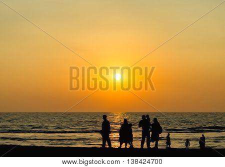 Big family silhouette meeting vivid orange sunset ocean horizon abstraction