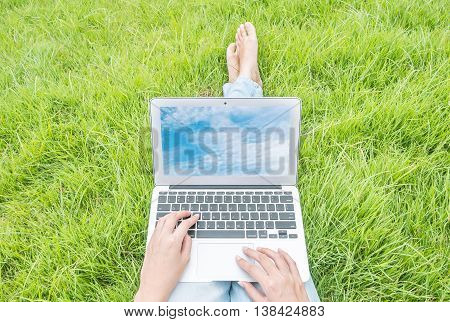 Asian woman sitting on grass floor in the garden textured background for use a notebook computer with blue sky in screen of notebook