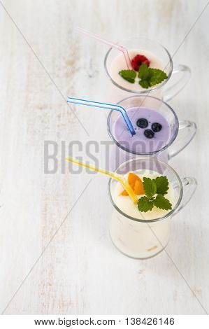 Smoothies with fresh berries on a wooden table