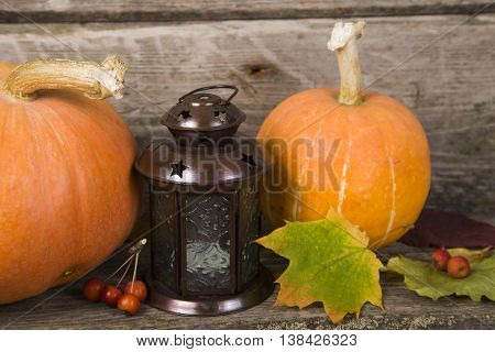Pumpkins,lantern And Fall Leaves On A Wooden Table