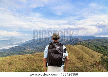 Male tourist with Back packer looking tropical forest