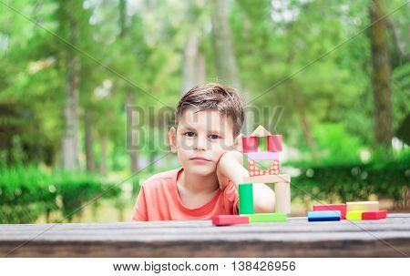 Preschool child build a tower of colorful wooden building blocks in the park.