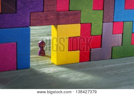 Abstract man in the doorway. Colorful wall of wooden puzzles. Construction of Tetris shapes.