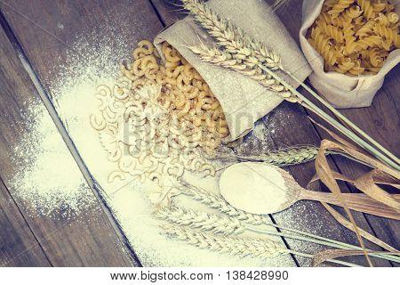 Uncooked Italian Pasta Farfalle, Elbow Macaroni And Fusilli On Dark Wooden Background