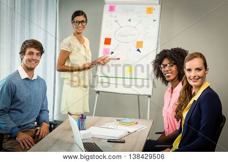 Portrait of woman discussing flowchart on white board with coworkers in the office