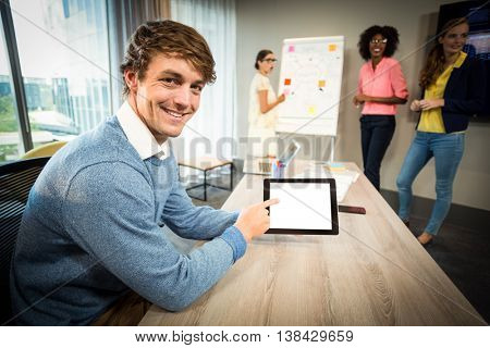 A colleague using digital tablet while coworkers discuss flowchart on whiteboard in the office