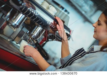 Tilt shot of female barista using espresso machine to pour coffee in cup at cafe
