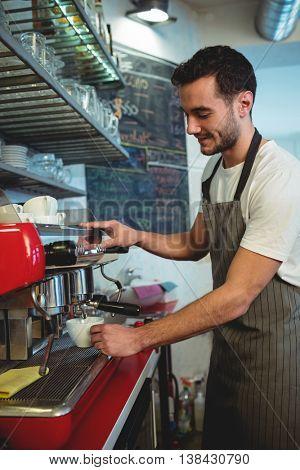 Happy male barista using espresso maker at cafe
