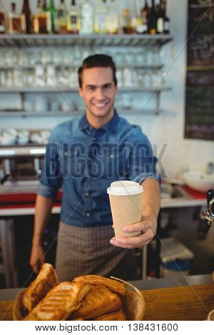 Portrait of happy young male barista offering coffee in disposable cup at cafe