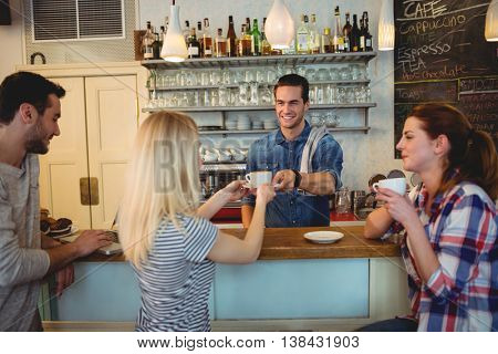 Handsome waiter serving coffee to young customer with friends at cafeteria