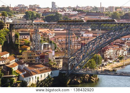 PORTO, PORTUGAL - JUL 12, 2016: Train of Porto Metro on Dom Luis iron Bridge in Old Town. The network has 6 lines and reaches seven municipalities within the metropolitan Porto area.