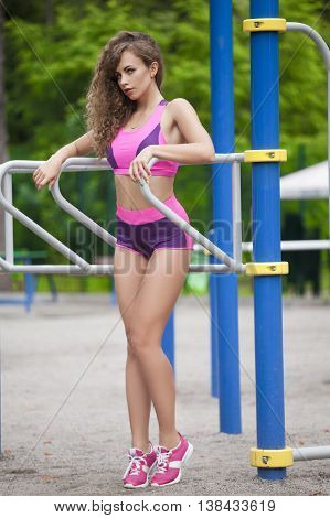 Beautiful and athletic girl standing near the bars . In a sports suit