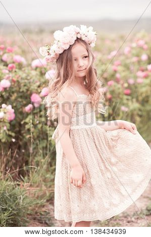 Smiling kid girl 4-5 year old posing in rose garden outdoors. Wearing stylish dress and wreath with flowers. Summer portrait