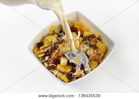milk pouring into bowl of corn flakes and cereals on white background - close up