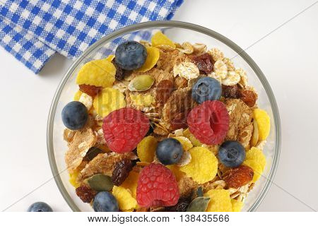 bowl of cereals and berry fruit and checkered napkin - close up