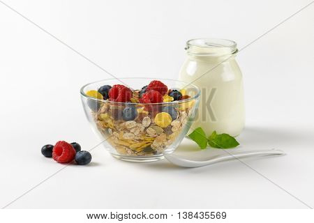 bowl of cereals and berry fruit and glass of white yogurt on off-white background with shadows