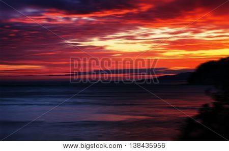 Horizontal vivid red orange vibrant sunset ocean horizon motion abstraction background backdrop