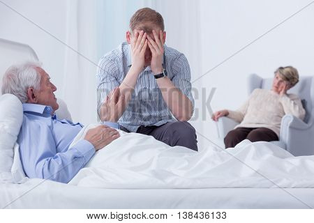 Upset grandson sitting by his grandfather's hospital bed hiding his face in his hands with a grandmother sitting in an armchair in the blurred background