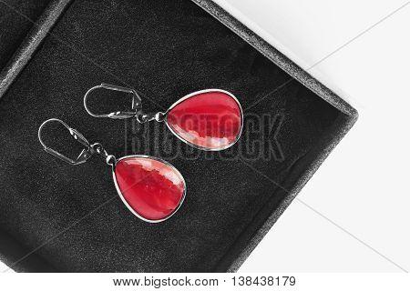 Red garnet earrings in black jewel box as a background