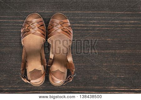 Pair of leather sandals on brown wooden floor as a background