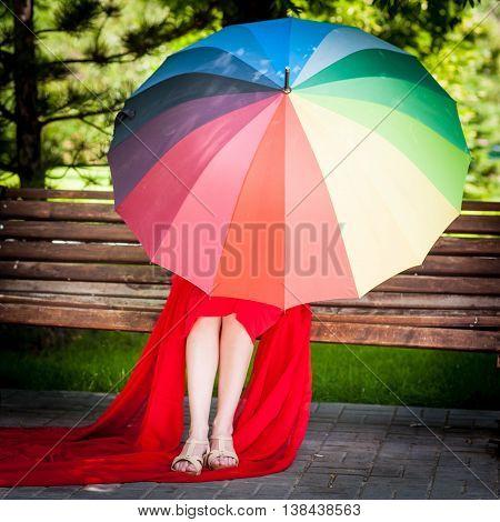 Young woman in red dress hidden under umbrella
