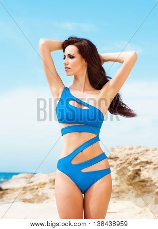 Beautiful, fit and sexy girl in blue swimsuit posing on a beach at summer. Sea and sky background.