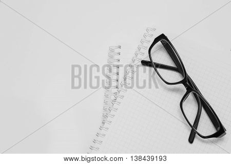 black plastic glasses on the opened notepad. View from above.