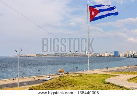 HAVANA, CUBA - MARCH 17, 2016: View of a huge Cuban flag and the Malecon from Hotel Nacional in Havana the capital of Cuba