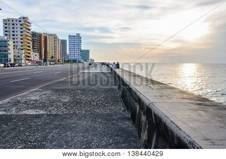 HAVANA, CUBA - MARCH 17, 2016: Sunset in the Malecon Avenue where people socialize in Havana the capital of Cuba