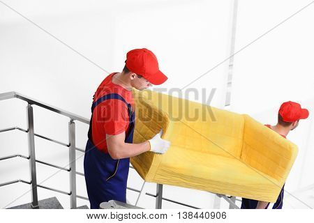 Two male workers with yellow couch on staircases