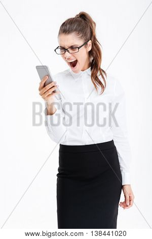 Irritated furious young business woman using mobile phone and shouting over white background