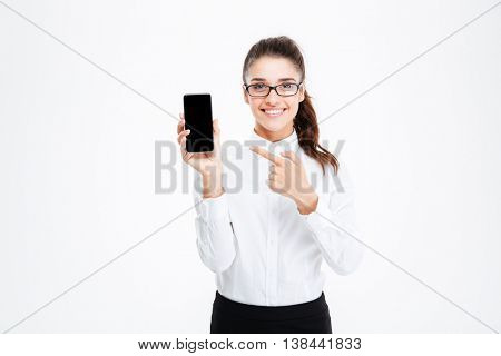 Happy pretty young businesswoman in glasses pointing on blank screen cell phone over white background