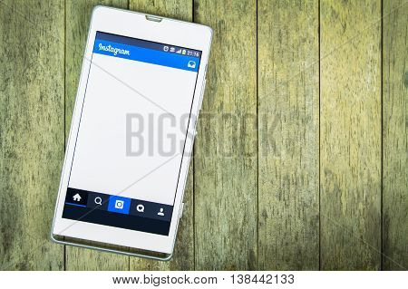 BUNG KAN THAILAND - FEBRUARY 19 2016: smart phone display instagram app on wood background space for caption