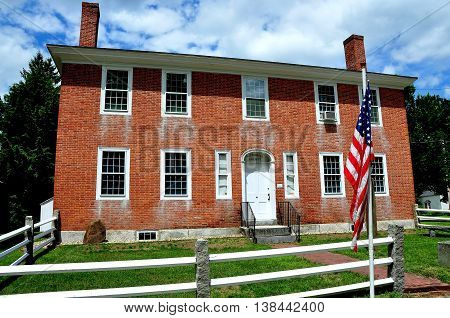 Hancock New Hampshire - July 11 2013: An American flag stands in front of the Hancock Historical Society housed in an 1809 brick home