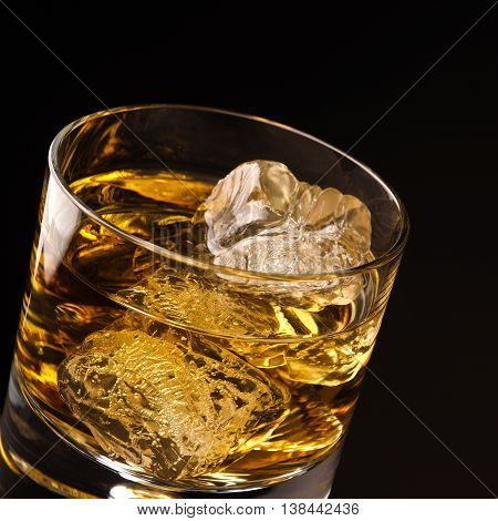 Close up shot of a glass of whiskey with ice cubes on a dark background