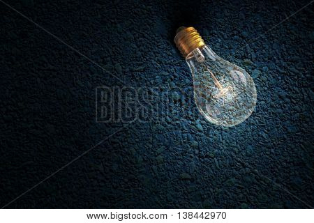 Glowing bulb on stone surface . Mixed media