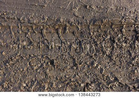 Imprint of wheel on dirt wet road.